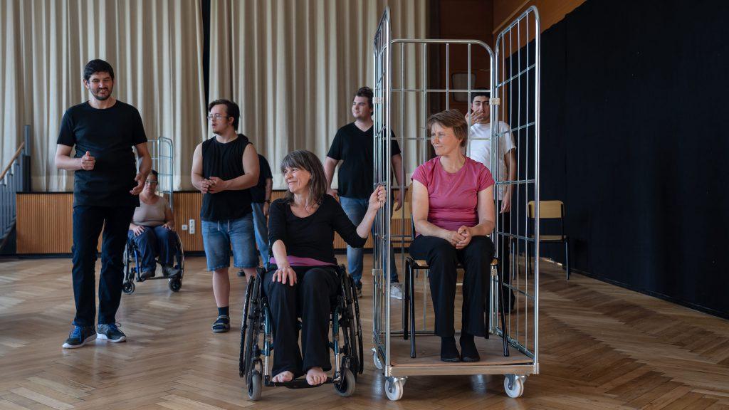 Eine Tänzerin im Rollstuhl legt Ihre Hand an einen Rollcontainer, in dem eine weitere Tänzerin sitzt